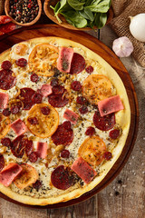 Meat and tomato pizza on wooden table