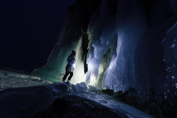 Foto auf Acrylglas Schwarz Surreal landscape with woman exploring mysterious ice grotto cave. Outdoor adventure. Girl exploring huge icy cave, dark majestic landscape. Magical silhouettes on background of illuminated ice blocks