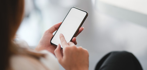Cropped shot of businesswoman using smartphone in blurred office room