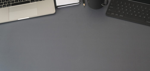Wall Mural - Top view of modern workplace with laptop computer and office supplies on dark grey table