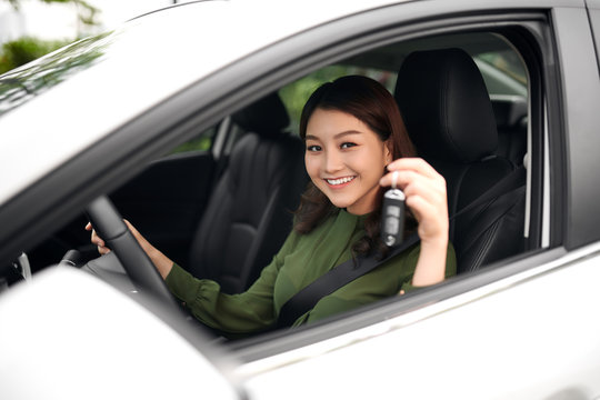 Beautiful young girl driver with car key in hand, happy owner of a new automobile