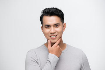 Happy smiling young handsome Asian man face with hand touching chin studio shot isolated