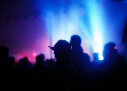Blurry shot of a lot of people at a concert with spotlights in the background