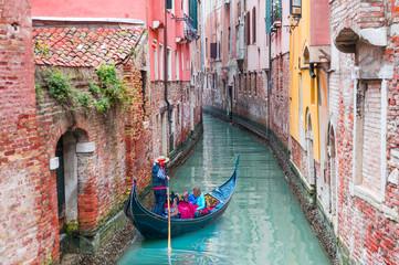 Foto op Aluminium Gondolas Venetian gondolier punting gondola through green canal waters of Venice Italy