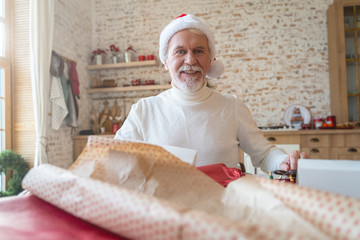 Cheerful aged male preparing presents for Christmas