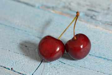 Wall Mural - Ripe red cherries on a blue wooden background.