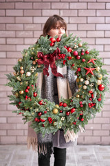 Beautiful festive wreath of fresh spruce in woman hands. Xmas circlet with red and gold ornaments and balls. Christmas mood. Brick wall on background.