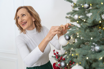 Pleased brunette female putting balls on tree