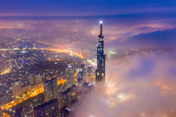 Aerial view of Saigon cityscape at night with misty sky