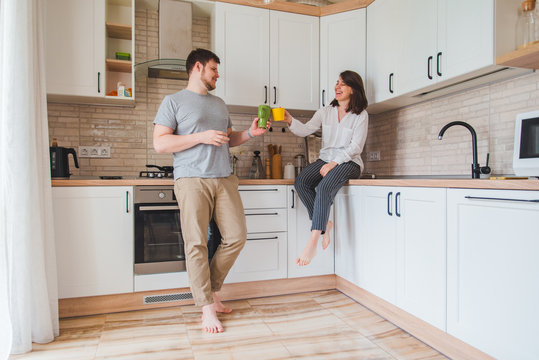 smiling man with woman at kitchen drinking tea