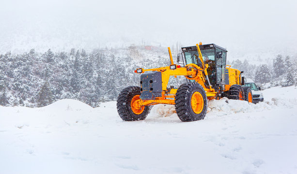Bulldozer cleans snow-covered road through the forest.