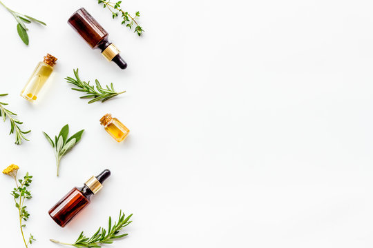 Essential oils and fresh herbs on white background top view pattern frame copy spacee