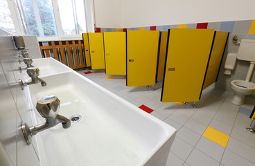 taps of washbasin and yellow doors in the bathroom of a nursery