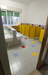inside a school bathroom  without children and with white sinks