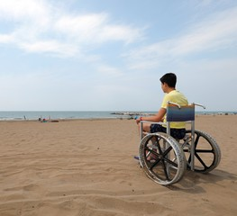 young boy on the special  wheelchair looks at the sea