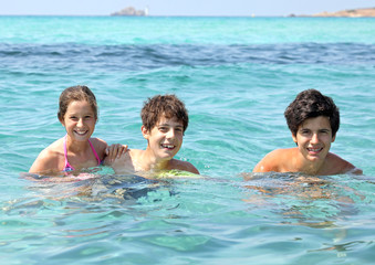 three smiling brothers in the clear water during a fun summer va