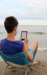 Young boy reads the ebook on the beach in summer