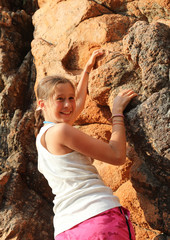 smiling little girl as she climbs the red rock of the mountain
