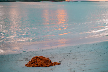 Abandoned orange beach towel sits on the sand near the water at a resort in the Maldives. Concept for litter, trash, beach vacation