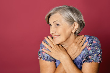 Close up portrait of beautiful senior woman isolated on red background