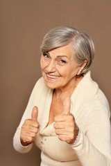 Close up portrait of beautiful senior woman with thumbs up