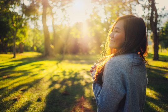 Portrait image of a beautiful asian woman standing among nature in the park before sunset