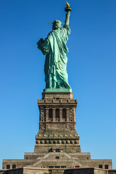 Statue of Liberty back side on a clear blue sky day, Ellis Island, New York, United States of America.