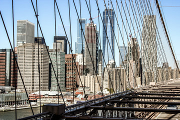 Cinematic look of the skyline of Lower Manhattan, New york. Taken from the Brooklyn Bridge with the steel cables crossing the image, United States of america.