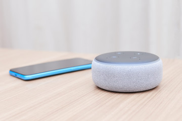amazon echo dot third generation, white, with a blue smartphone out of focus, on a light wooden table