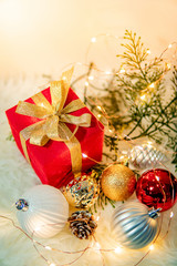 Christmas decoration on white hairy carpet with illuminated lights. Gift box with ribbon, Xmas ball ornament and Christmas tree branch on fluffy rug. Present and decorative object for New Year holiday