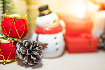 Christmas decoration concept. Pine cone, snowman toy, gift box and Christmas ball on wooden table. Decorative objects for Xmas and New Year holiday. Ornament for Festive season and celebration