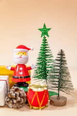 Christmas decoration concept. Santa Claus toy, gift box, pine cone and mini Christmas tree on the table. Decorative objects for Xmas and New Year holiday. Ornament for Festive season and celebration