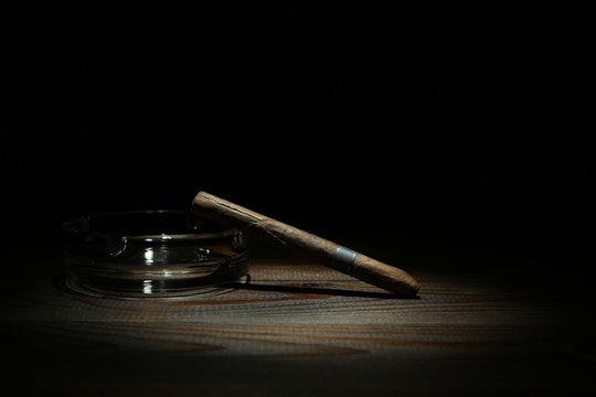 cigar and ashtray on dark background