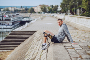 Fotomurales - Side view of caucasian handicapped sportsman in sportswear and with artificial leg sitting on quay and looking away.