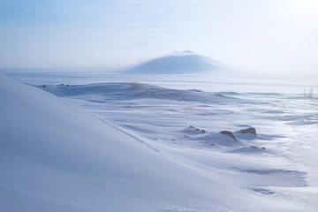 Winter arctic landscape with snow covered tundra and hills. Very cold frosty weather in April in the far north of Russia. Location place: Chukotka, Siberia, Russian Far East. Polar region.