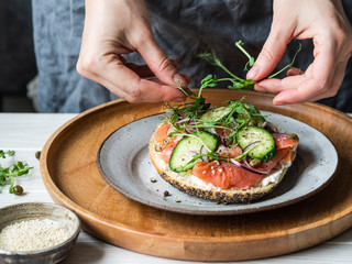 Healthy toast with cream cheese, salmon, fresh cucumber, capers, red onion, black pepper and and an uncertain woman lays on sandwich pea sprouts .