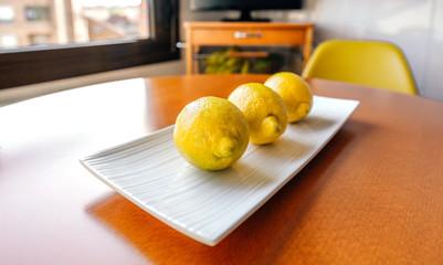 Still life of three lemons on a white plate