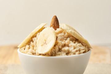Oatmeal breakfast bowl. Organic healthy food with candied fruit raisins, nuts, banana