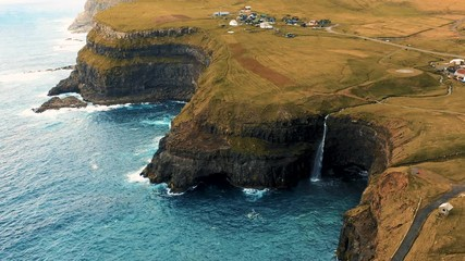 Wall Mural - Flying above Gasadalur village and Mulafossur waterfall in the Faroe Islands
