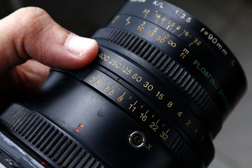 Aperture and shutter speed adjustment ring on the lens of a medium format film camera