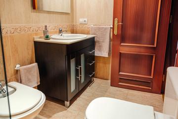 Interior of tidy bathroom with washbasin cabinet