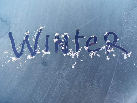Winter written in the ice on a car windscreen on a cold frosty morning