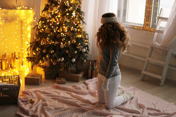 beautiful woman with dark hair in cozy clothes posing near decorated Christmas tree at home