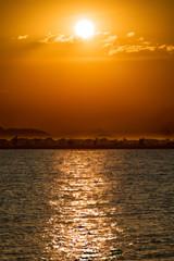 Sun, clouds, lake malawi and coastline with orange sky