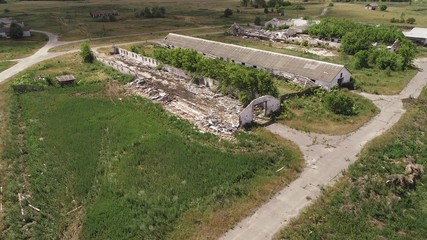 Flying over an abandoned and destroyed farm. Ruined cowsheds and farmyard.