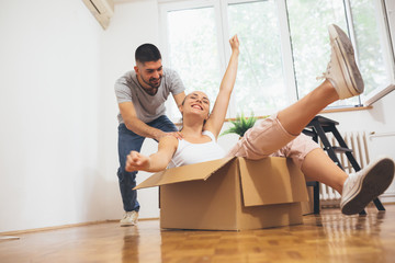 romantic couple having fun while moving in their new home