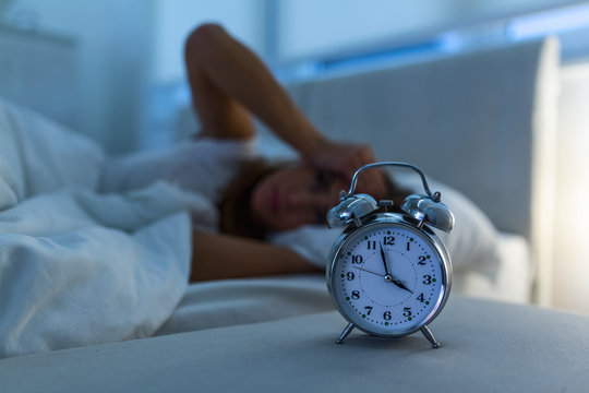 young beautiful woman at home bedroom lying in bed late at night trying to sleep suffering insomnia sleeping disorder or scared on nightmares looking sad worried and stressed