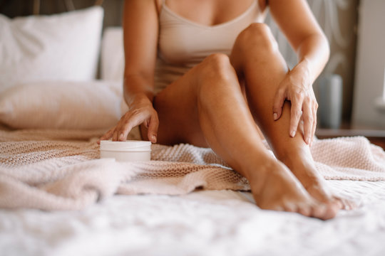 Woman applying body cream on her leg in bedroom. Close up