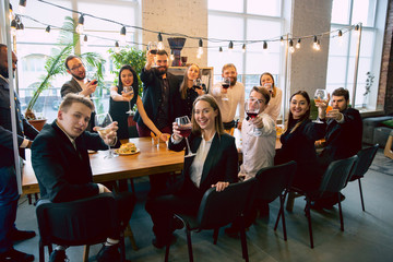 Happy co-workers celebrating while company party and corporate event. Young caucasian people in business attire cheering, laughting. Concept of office culture, teamwork, friendship, holidays, weekend.