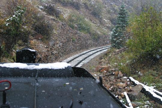 Stem locomotive and rail tracks on a rainy, snowy day